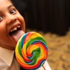 A young boy enjoys a giant lollypop.
